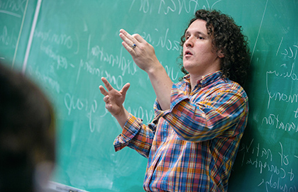 A business professor lectures in front of a blackboard